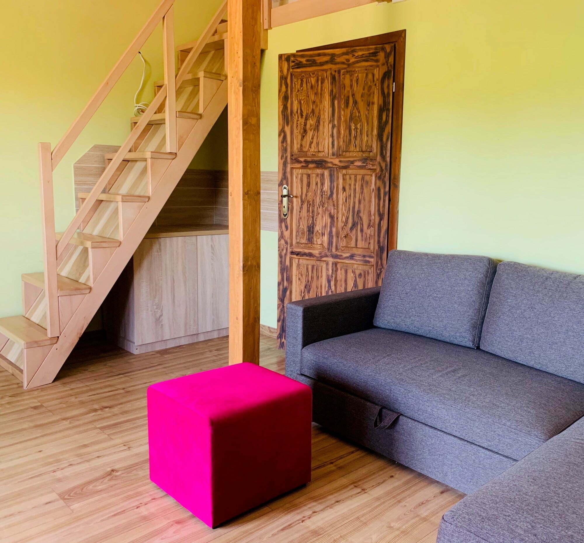 """Do Waszej dyspozycji mamy  3 apartamenty, a każdy z nich może pomieścić od 2 do 5 osób. Wykończenia elementami drewnianymi w stylu rustykalnym sprawiają, że pokoje są przytulne. W wyposażeniu każdego z nich jest kuchnia z prawdziwego dębowego drewna.   Czym byłaby agroturystyka bez sali kominkowej? Nasza jest wielofunkcyjna, bo oprócz tego, że jest przytulna, wygodna i ma kominek, to znajduje się w niej też biblioteka z książkami dla dorosłych i dla dzieci oraz miejsce na inne aktywności.  Do gospodarstwa przylega nasz prywatny las, który zachęca do spacerów, oferując przyjemny cień w upalne letnie dni i bogactwo swego runa, zwłaszcza jesienią. Wokół można obserwować pasące się konie i osły. Jest sielsko. A może filozofia """"dolce far nulla"""", czyli słodkie nic robienie?"""